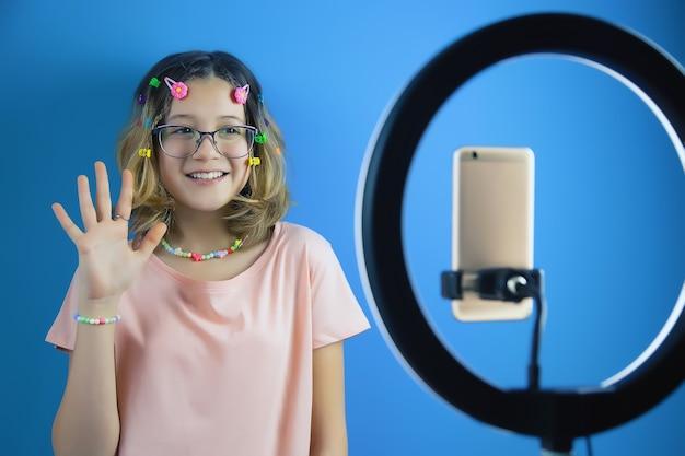 Una blogger adolescente conduce una trasmissione online sul suo smartphone per i social network e gli abbonati agli account
