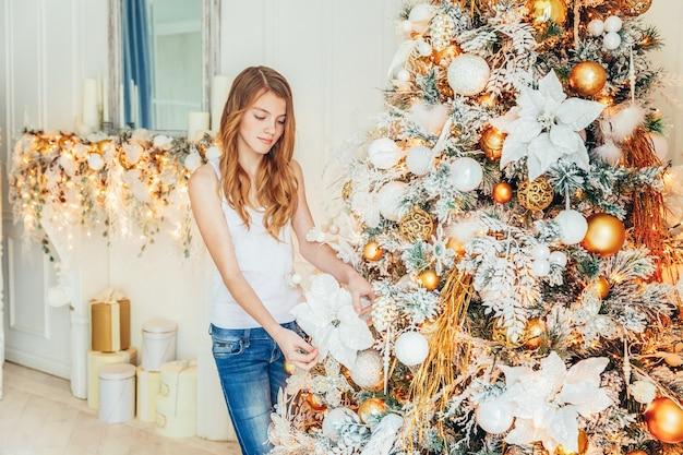 Adolescente che decora l'albero di natale alla vigilia di natale a casa. giovane donna in una stanza luminosa con decorazioni invernali. famiglia felice a casa. natale capodanno dicembre per il concetto di celebrazione.