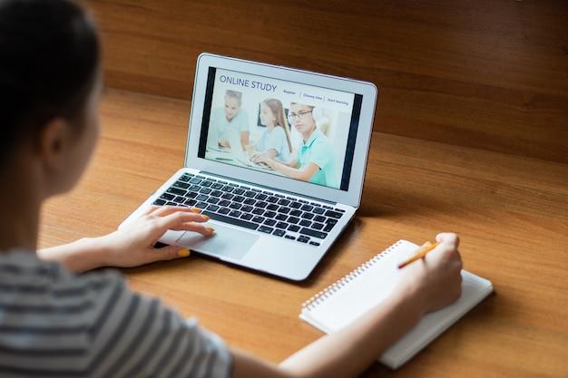 Ragazza adolescente che entra nel sito web educativo mentre si scorre la homepage con l'immagine della rete di scolari