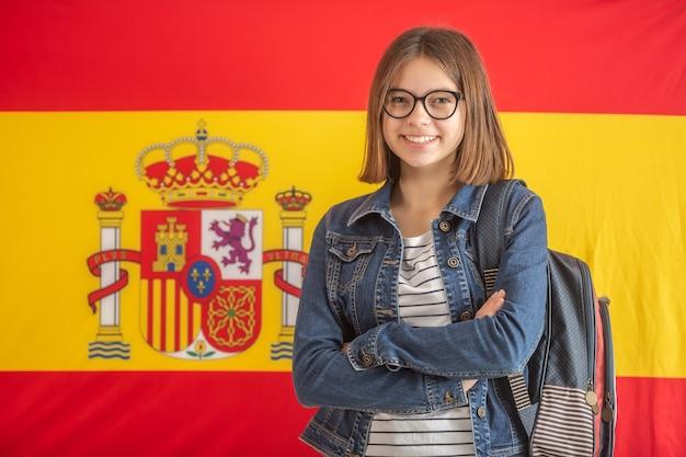 L'adolescente con gli occhiali indossa lo zaino e sta sorridendo davanti alla bandiera della spagna.