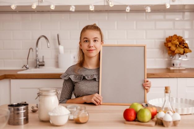 Ragazza adolescente in un vestito grigio sta per cucinare una torta di mele tradizionale nella nuova cucina e tiene una griglia di legno vuota con uno sfondo grigio