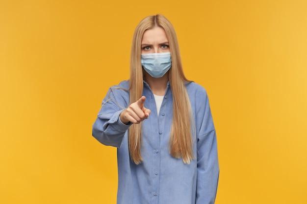 Ragazza adolescente, donna dall'aspetto felice con i capelli lunghi biondi. indossare maglietta blu e mascherina medica. concetto di persone ed emozione. puntando il dito nella fotocamera isolata su sfondo arancione