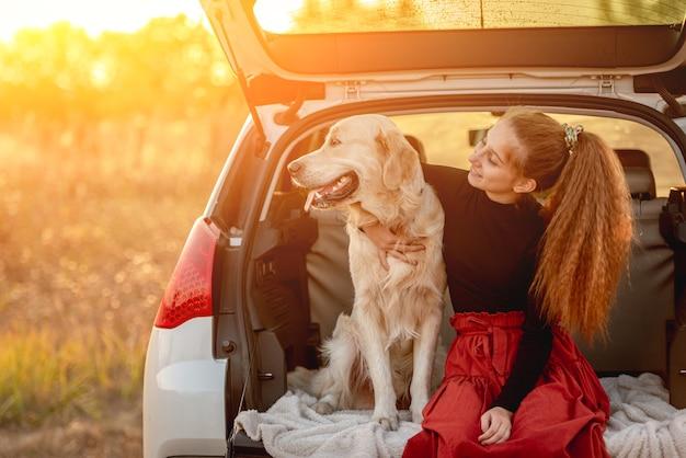 Adolescente che abbraccia il cane nel bagagliaio dell'auto