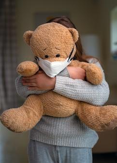 Ragazza adolescente abbracciando orsacchiotto con maschera per il viso.