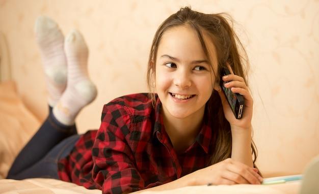 Adolescente sdraiato in camera da letto e parlando al telefono