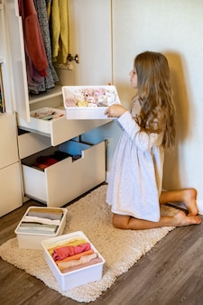 L'adolescente arrotolato usa il metodo marie kondos mettendo l'abbigliamento nell'armadio