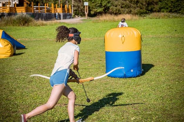 Ragazza adolescente in esecuzione con arco e frecce durante una partita di tag di tiro con l'arco