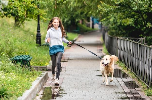 Ragazza adolescente in esecuzione con il golden retriever cane nel parco dopo la pioggia