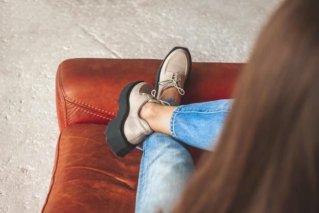 Adolescente che si siede sulla sedia di pelle in jeans e scarpe da ginnastica urbane. foto di street fashion e look concept