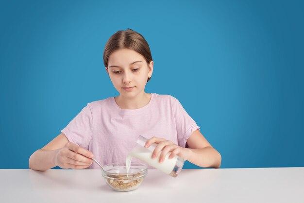 Ragazza adolescente seduto a tavola e l'aggiunta di latte in cereali mentre si fa colazione