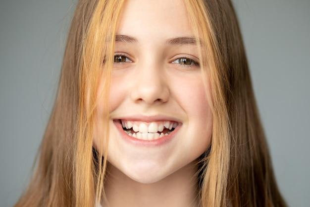 Ragazza adolescente sorridente e mostrando denti bianchi frastagliati, medicina dentale e assistenza sanitaria