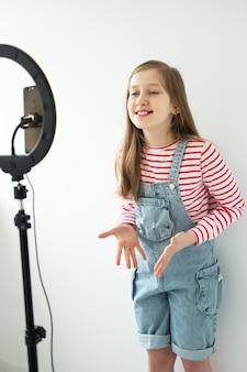 Adolescente social media blogger registrazione video parlando guardando smartphone su treppiede con luce ad anello.