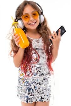 Ragazza adolescente in abito scintillante e occhiali da sole giallo brillante, con grandi auricolari bianchi, ascoltando musica con smartphone nero e bottiglia con succo d'arancia in mano isolato