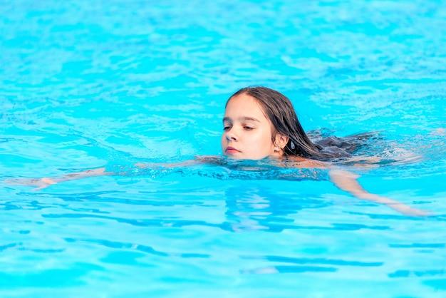 L'adolescente nuota nell'acqua cristallina di una piscina durante una vacanza in un caldo paese tropicale