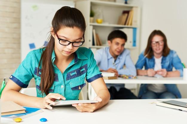 Adolescente che utilizza compressa nell'aula moderna