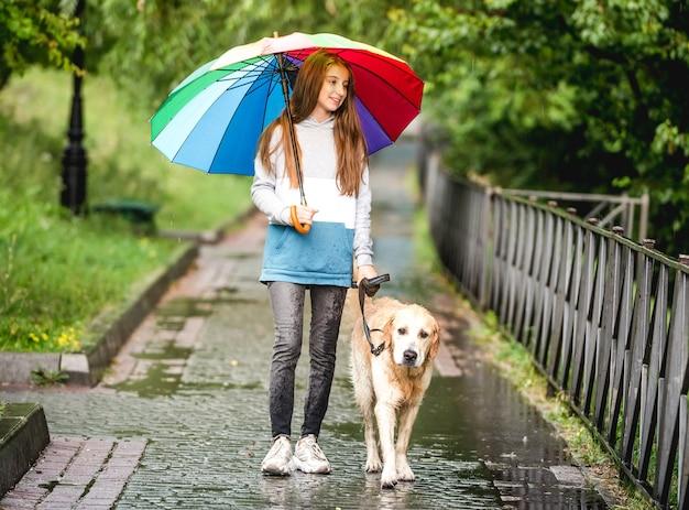 Adolescente che cammina con il cane golden retriever al giorno di pioggia
