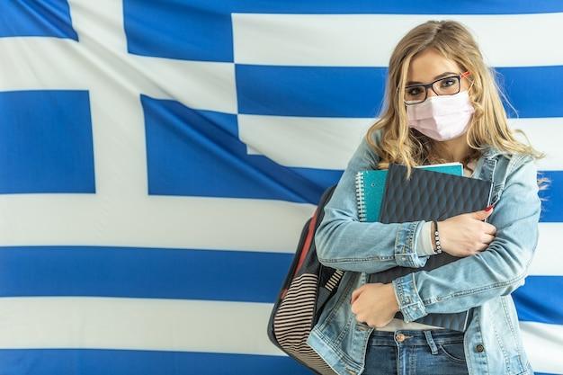 L'adolescente che indossa la protezione del coronavirus tiene i libri di testo e indossa lo zaino con la bandiera greca nella parte posteriore.