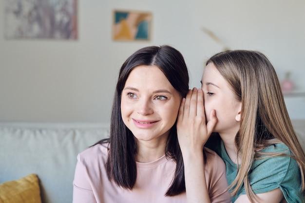 Ragazza adolescente sussurrando pettegolezzi all'orecchio delle madri condividendo il suo segreto, il concetto di privacy