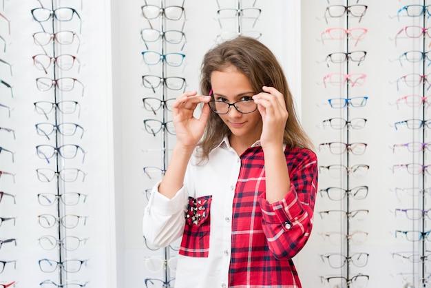 Ragazza adolescente con occhiali neri in piedi nel negozio di ottica