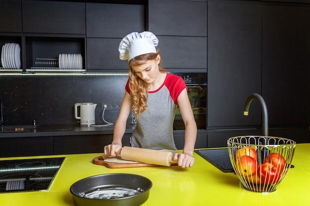 Adolescente con cappello da chef, mattarello che prepara l'impasto, cuocere la torta di mele casalinga per le vacanze in cucina. giovane donna che cucina cibo sano a casa e si diverte. cibo, alimentazione sana, concetto di famiglia