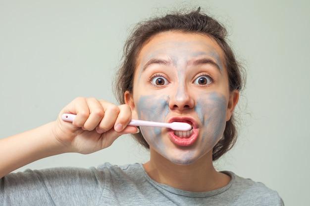 Una ragazza adolescente con una maschera cosmetica sul viso si lava i denti
