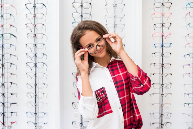 Ragazza adolescente con gli occhiali in piedi nel negozio di ottica
