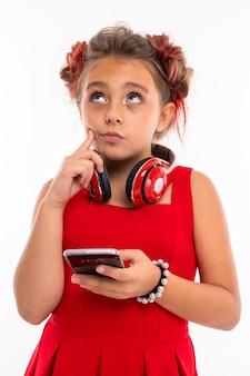 Ragazza adolescente con lunghi capelli biondi, punte tinte di rosa, imbottite in due ciuffi, in abito rosso, con cuffie rosse, braccialetto, in piedi e tenendo in mano il telefono e pensando