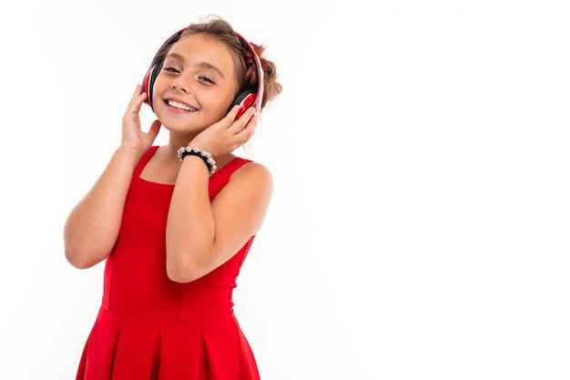 Ragazza adolescente con lunghi capelli biondi, punte tinte di rosa, imbottita in due ciuffi, in abito rosso, con cuffie rosse, braccialetto, in piedi e ascoltare musica