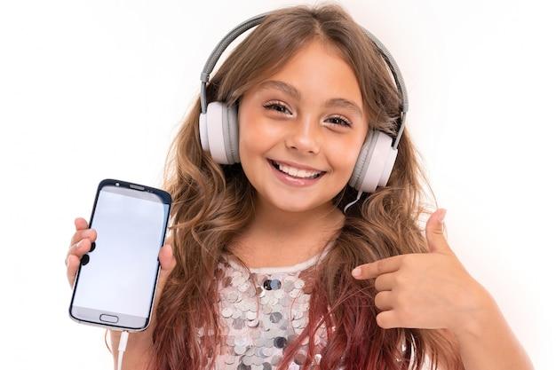 Adolescente con lunghi capelli biondi tinti di punte rosa, in abito chiaro lucido, in piedi con le cuffie e tenendo in mano il telefono