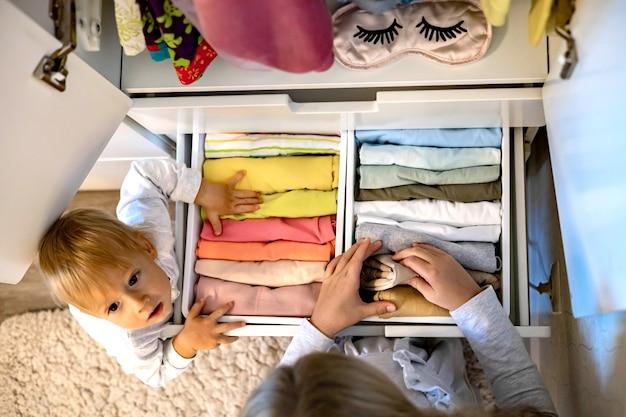 L'adolescente con i capelli lunghi arrotolati usa il metodo marie kondos mettendo l'abbigliamento nell'armadio