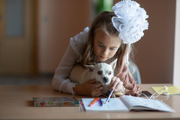 Ragazza adolescente con cane da compagnia facendo i compiti utilizzando il telefono seduto dalla scrivania in camera accogliente concetto di apprendimento formazione online sul posto di lavoro comunicazione a distanza con lo smartphone