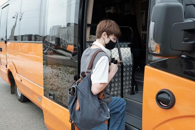 Ragazza adolescente con i capelli corti che indossa una maschera facciale che tiene la cartella mentre sale sul bus contemporaneo