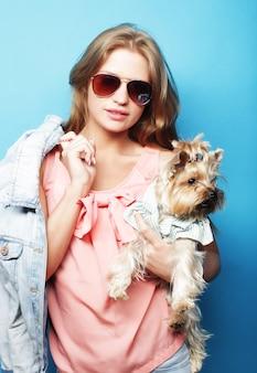 Adolescente con yorkshire terrier su sfondo blu