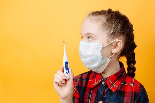 Una ragazza adolescente su una parete gialla tiene in mano un termometro e distoglie lo sguardo