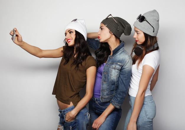 Amici di ragazze adolescenti in abito hipster che prendono selfie su un telefono