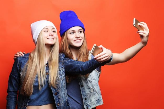 Ragazze adolescenti in cappelli prendendo selfie