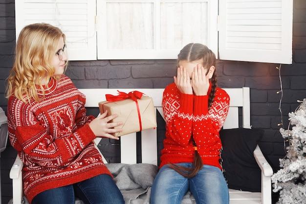 Le ragazze adolescenti con un maglione rosso di natale regalano scatole regalo mentre sono sedute su una panchina.