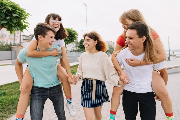 Amici di scuola adolescenti divertendosi piggyback all'aperto