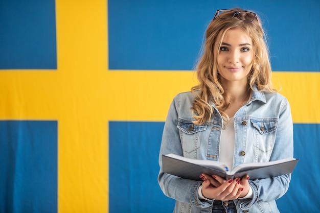 Studente adolescente con libri aperti sta con bandiera svedese dietro di lei.