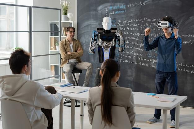 Studente adolescente con auricolare vr in piedi vicino alla lavagna di fronte ai suoi compagni di classe e dimostrando le abilità del robot nelle vicinanze