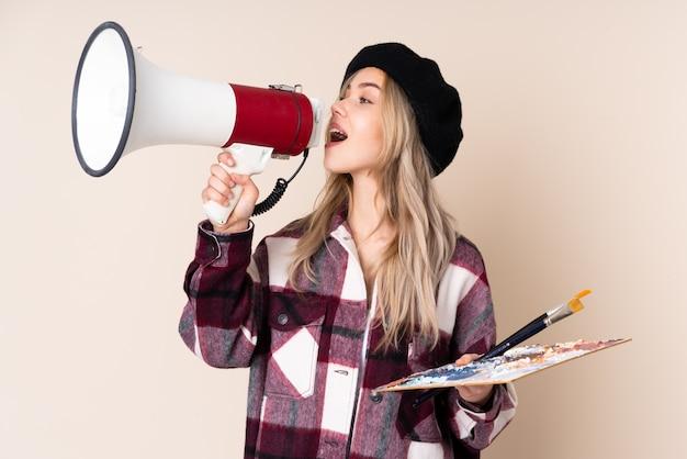 Ragazza dell'artista dell'adolescente che tiene una tavolozza sulla parete blu che grida tramite un megafono