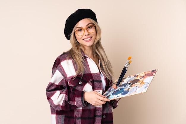 Ragazza dell'artista dell'adolescente che giudica una tavolozza isolata sulla parete blu con i vetri e sorridere