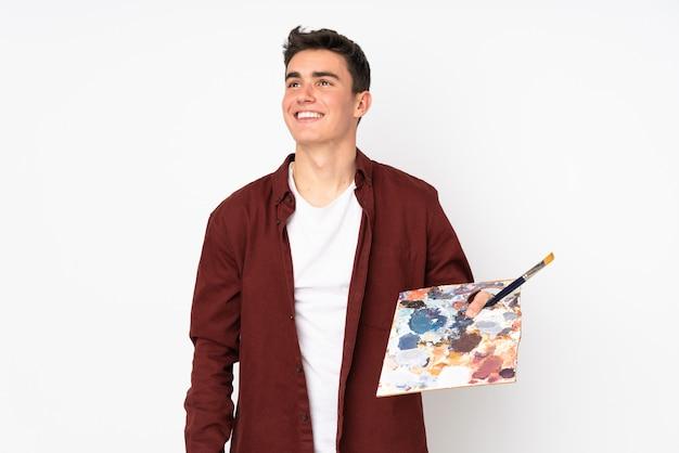 Uomo dell'artista dell'adolescente che giudica una tavolozza isolata sul fondo bianco che cerca mentre sorridendo