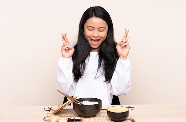Ragazza asiatica dell'adolescente che mangia alimento asiatico sulla parete beige con le dita attraversate