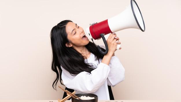 Ragazza asiatica dell'adolescente che mangia alimento asiatico isolato su fondo beige che grida tramite un megafono