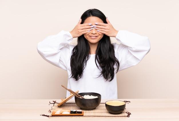 Ragazza asiatica dell'adolescente che mangia alimento asiatico isolato sugli occhi beige della copertura con le mani