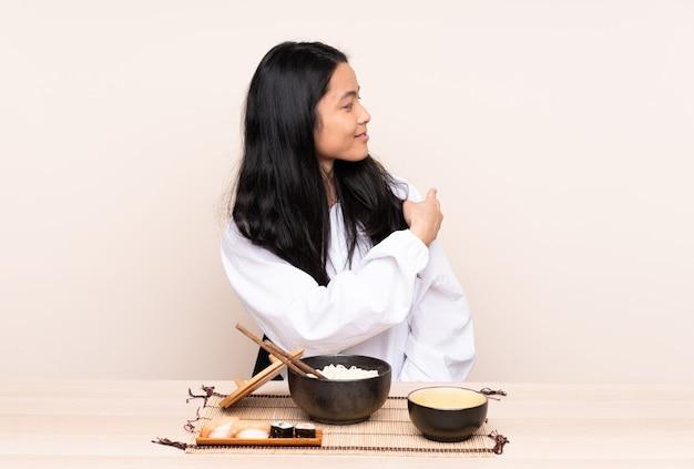 Ragazza asiatica dell'adolescente che mangia alimento asiatico isolato su beige che indica indietro