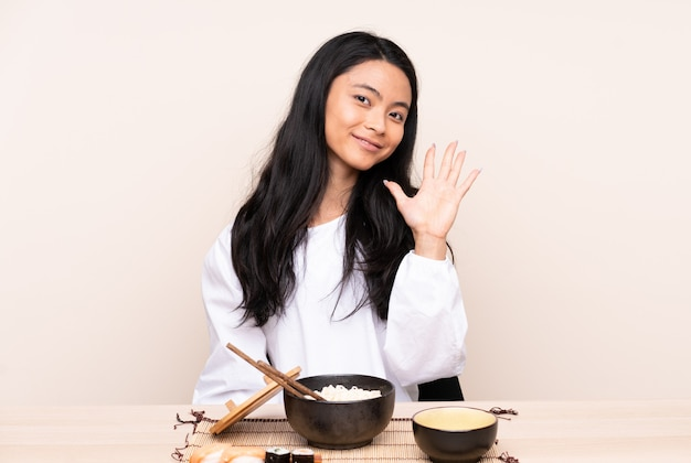Ragazza asiatica dell'adolescente che mangia alimento asiatico isolato sulla parete beige che conta cinque con le dita
