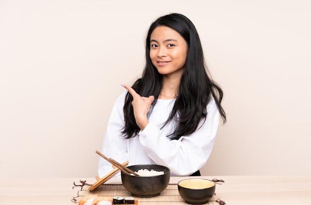 Ragazza asiatica dell'adolescente che mangia alimento asiatico isolato sulla parete beige che indica il lato per presentare un prodotto