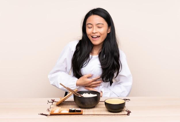 Ragazza asiatica dell'adolescente che mangia alimento asiatico isolato sulla parete beige che sorride molto